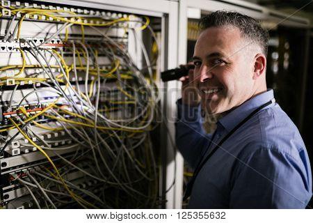 Technician shining light on server at the data centre