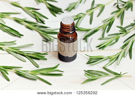 Rosemary essential oil. Fresh rosemary herb sprigs scattered, apothecary bottle.