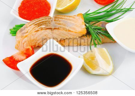 healthy fish cuisine : grilled pink salmon steaks with red caviar lime and sauces on white dish isolated over white background
