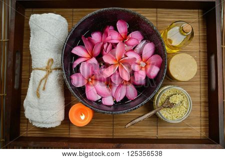 Spa setting with candle ,towel, oil frangipani in bowl with mat texture