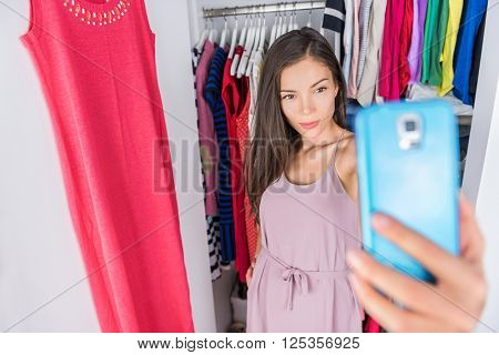 Smart phone selfie Asian woman in clothes closet of home bedroom or  store dressing room next to clothing rack. Shopping girl taking a photo of her outfit using smartphone fashion app. Social media.