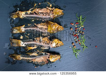 top view of fish skeleton bones and flavor peppers on slate background close up