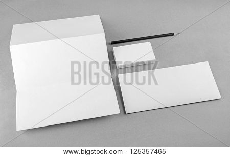 Photo of blank stationery set on gray background. Mock-up for branding identity. For design presentations and portfolios. Grayscale image.