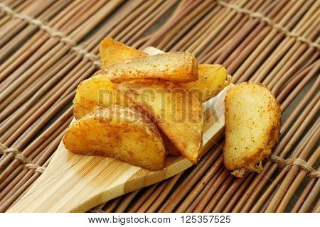 Fried potato wedges on wooden spatula. Close up.