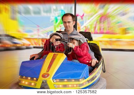 Father And His Two Sons, Having A Ride In The Bumper Car