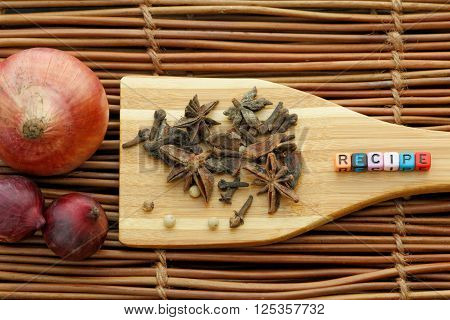 Clove,coriander,star anise and alphabet block forming a word RECIPE on wooden spatula with small and big onion