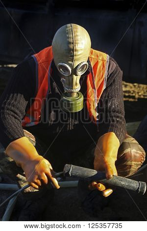 Worker in special protective clothing masks and gloves works in a dangerous environment