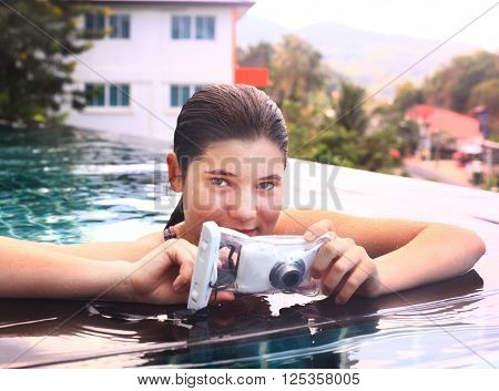 teenager girl i in water in swimming pool with camera in protective waterproof slipcover cover for underwater photo shooting footage