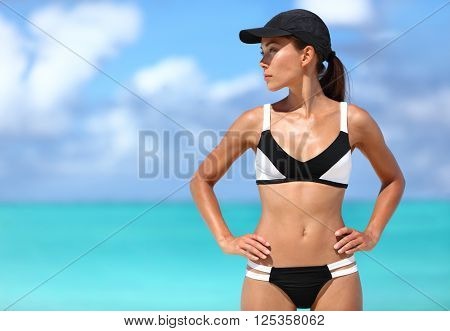 Sexy sporty bikini woman ready for beach sports. Active healthy Asian girl model standing against ocean background on sunny summer travel vacation.