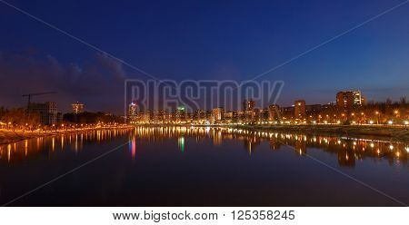 Night city reflection on the river in Donetsk. Ukraine