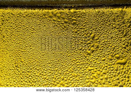 When chilled beer is poured into a glass cup a layer of water drops is formed covering the whole body of the cup.