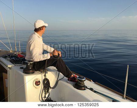Young man sailing yacht yachtsman holding hands rope vacation sail holidays people travel