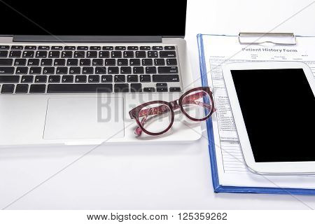 Doctor's desk with computer notebook tablet glasses and patient history form on white table with copy space