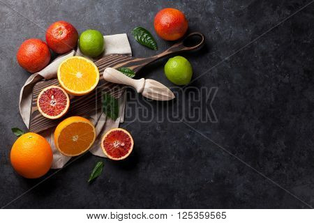 Fresh citruses on dark stone background. Oranges and limes. Top view with copy space