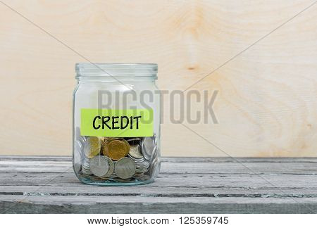 Label on a glass jar with the inscription - credit. Glass jar with coins. Financial concept on wooden background