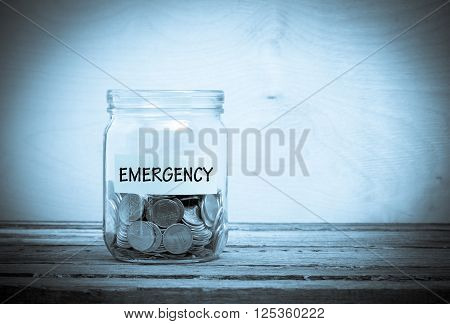 Label on a glass jar with the inscription - emergency. Glass jar with coins. Financial concept on wooden background
