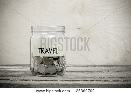 Label on a glass jar with the inscription - travel. Glass jar with coins. Financial concept on wooden background