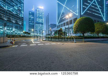 clean road against illuminated buildings in shanghai.