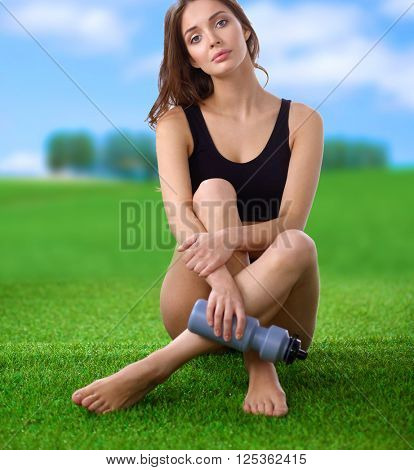 Young female athlete sitting on grass after exericise and holding a water bottle