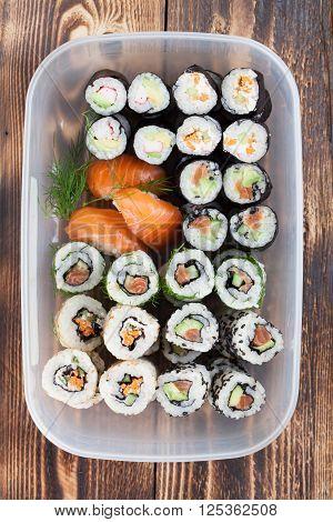 Sushi set in a plastic box. Maki uramaki and nigiri sushi.