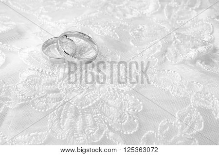 Wedding rings on wedding cards on a white wedding dress