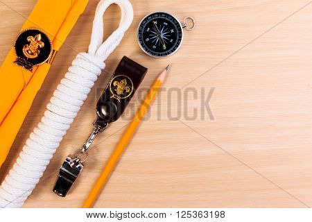 Metal Whistle, Scout Scarf, Rope, Pencil And Compass On Wooden Background.