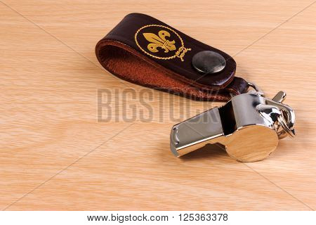 Metal Whistle With Leather Keychain On Wooden Background.