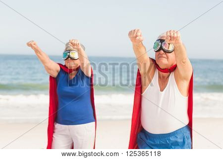 Senior couple wearing superman costume on a sunny day
