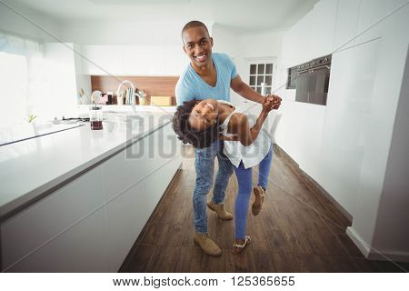 Happy couple dancing in the kitchen and looking at the camera