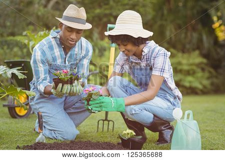 Happy couple in the garden holding flowers