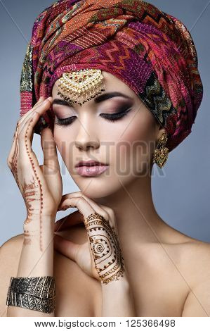 Beautiful fashion east woman portrait with oriental accessories- earrings bracelets and rings. Indian girl with henna tattoos and beauty jewels. Hindu model with perfect make-up. India. Asia
