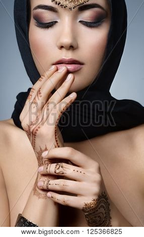Beautiful fashion east woman portrait.Asian girl in a black headscarf tenderly toucheszbeautiful slender fingers to his lips. East girl with henna tattoos.Hindu model with perfect make-up.India.Asia