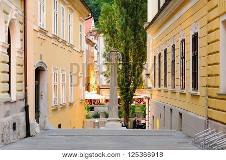 LJUBLJANA SLOVENIA - JULY 9 2009: Gledaliska stolba street with its theatrical Roman column and Ljubljanica river in the background