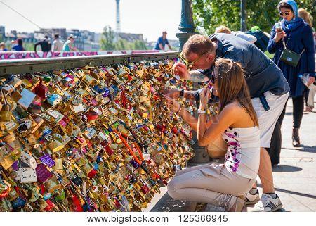 PARIS FRANCE - JUNE 8: Padlocks on the fence and people locking padlocks on Pont des Arts bridge in Paris on June 8 2015