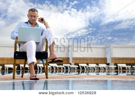 Portrait of a man with a laptop computer next to a swimming pool
