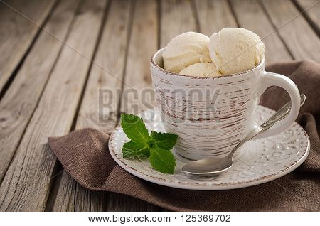 Vanilla ice cream in cup on rustic wooden background, selective focus, copy space