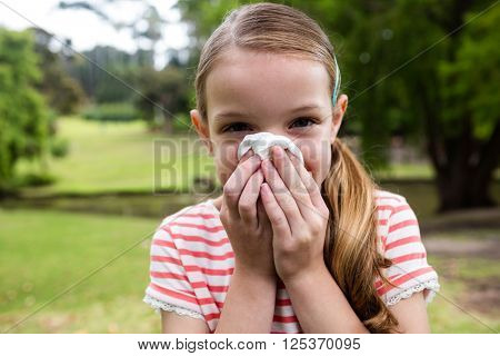 Sick girl covering her nose with tissue while sneezing in the park