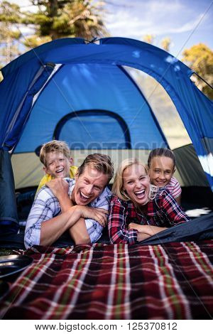 Portrait of happy family lying in a tent
