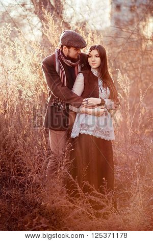 Old-fashioned stylish couple at sunset among the tall grass and bushes lit by the setting sun outdoors.