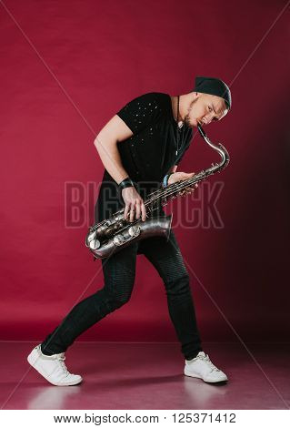 Young man playing saxophone. Man in modern clothes. Photo isolated on red background.