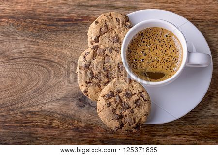 cup of coffee with chocolate cookies on wood