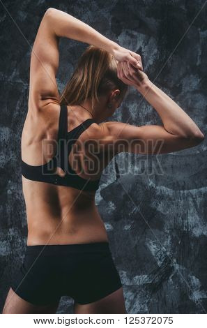 Close up image of female in sports clothing workout on grey background. Muscular female body. Photo from back