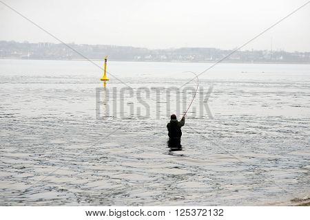 An angler gets bite - Standing in Little Belt close to Middelfart Funen Denmark.
