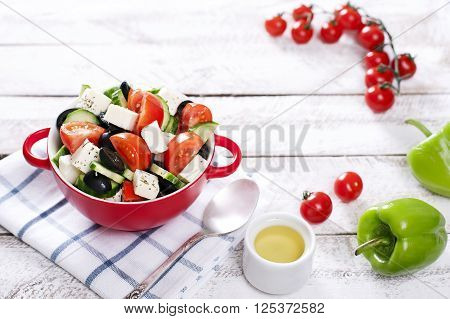 Greek salad in red boul and copy space