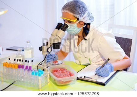 Food quality control expert inspecting at meat specimen in the laboratory. Selective focus