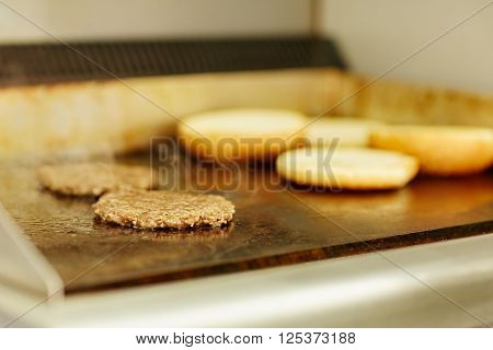 Two burger patties frying on a grill with hamburger buns toasting alongside