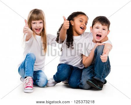 three funny children sitting on the floor with thumbs up