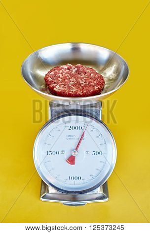 Retro scale against a yellow background with freshly minced red meat in it's bowl being weighed