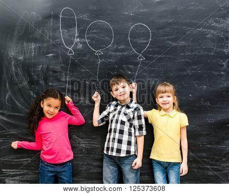 three joyful children keep imaginary balloons drawn on the blackboard