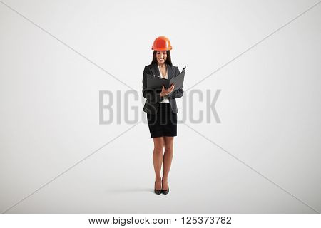 Smiling woman in formal wear and construction helmet looking on materials in black folder